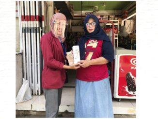 Siti Umairoh saat membagikan masker dan face shield